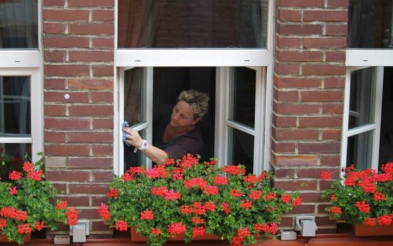 Frau putzt Fenster per Hand