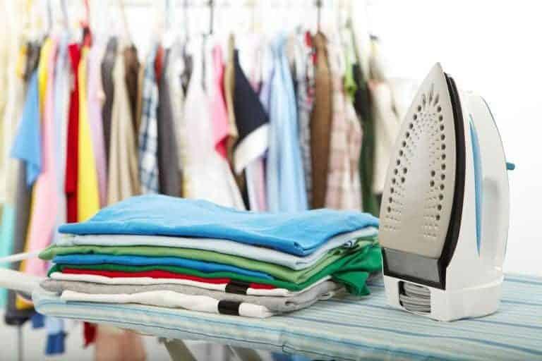 Bügeleisen neben gebügelter Kleidung