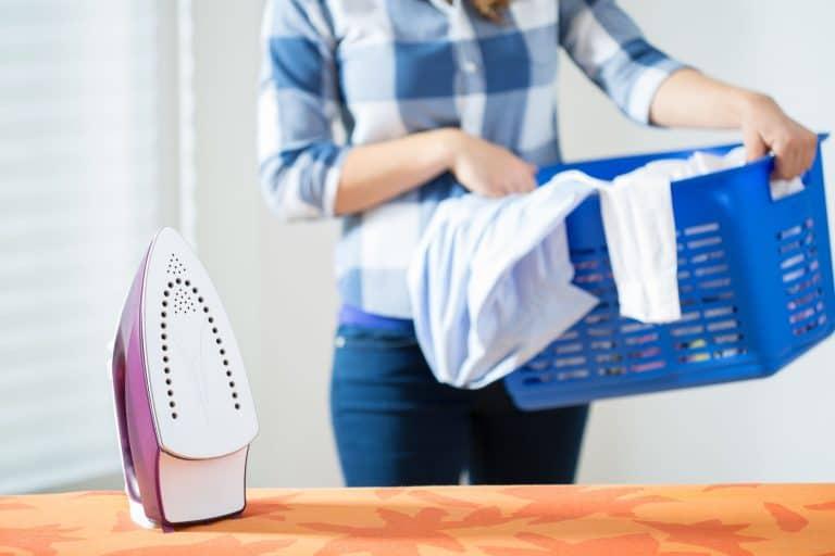 Frau mit Wäsche und Bügeleisen