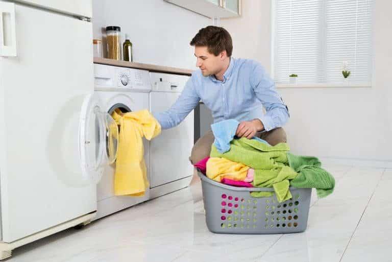 Mann räumt Waschmaschine ein