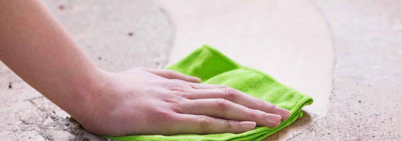 Frau wischt Dreck mit Mikrofasertuch weg