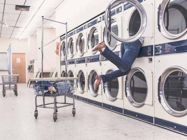 Jemand baumelt aus einer Waschmaschine im Waschsalon